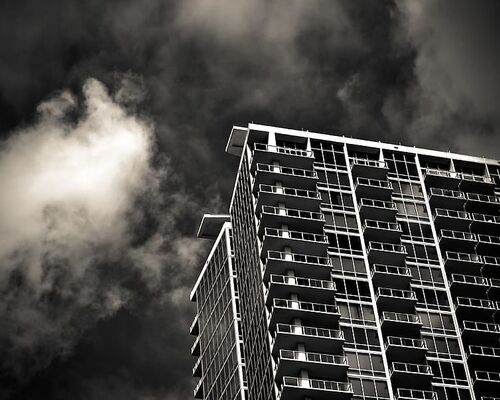 grayscale-photography-of-building-under-cloudy-sky